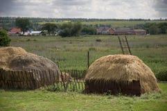 Nuages gris lourds dans le ciel froid d'automne au-dessus du village avec de petites maisons loin hayfield Il y a beaucoup de pil Image stock