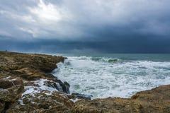 Nuages lourds avec les vagues orageuses battant contre des roches et des falaises Photographie stock libre de droits