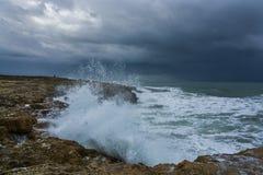 Nuages lourds avec les vagues orageuses battant contre des roches et des falaises Photographie stock