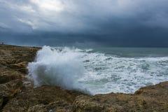 Nuages lourds avec les vagues orageuses battant contre des roches et des falaises Photos libres de droits