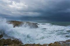 Nuages lourds avec les vagues orageuses battant contre des roches et des falaises Photo libre de droits