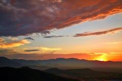Nuages magiques et coucher du soleil au-dessus de montagne photo stock