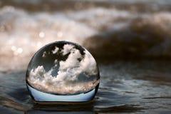 Nuages montrés par une boule en verre transparente sur le sable de plage photo libre de droits