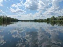 Nuages nageant en rivière Photo stock