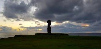 Nuages noirs au-dessus d'un moai au coucher du soleil, Hanga Roa, île de Pâques, Chili photo stock