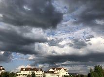 Nuages noirs au-dessus des maisons dans Ferney-Volter images stock
