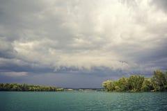 Nuages orageux au-dessus d'un lac vert photographie stock libre de droits