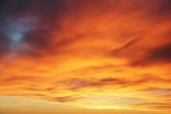 Nuages oranges sur le coucher du soleil Photographie stock