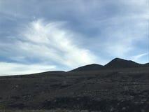 Nuages plumeux au-dessus de ciel bleu en montagnes Image stock