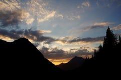 Nuages plumeux au-dessus des arêtes de montagne colorées par coucher du soleil Photographie stock libre de droits