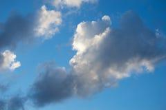 Nuages pluvieux blancs et gris sur un fond bleu Images stock