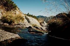 Nuages réfléchissant sur une rivière de montagne Photo libre de droits