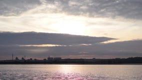 Nuages rétro-éclairés en ciel magnifique au-dessus de rivière et de ville clips vidéos