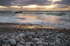 Nuages rapides, cailloux arrondis, et la mer au lever de soleil avec la soute de la défense WW2 Photos stock