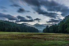 Nuages rayés au-dessus de vallée à distance au lever de soleil Photos libres de droits