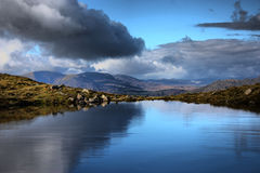 Nuages reflétés dans un lac calme vitreux Photo libre de droits