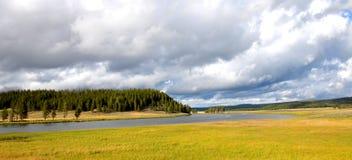 Nuages, rivière et prés en parc national en pierre jaune Photos stock