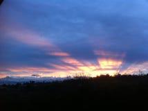 Nuages roses au-dessus de l'effet de ville et de lumière du soleil Images stock