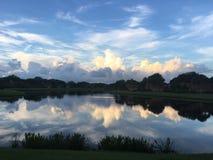 Nuages se reflétant au-dessus d'un lac clair pendant le matin Photographie stock libre de droits