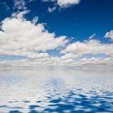 Nuages sur l'eau de mer Images stock