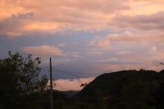 Nuages sur la plage de coucher du soleil de ville de montagne photographie stock libre de droits