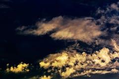 Nuages teintés jaunes de cumulus et de plume contre le ciel bleu égalisant de coucher du soleil photo libre de droits