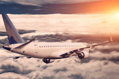 Nuages volants d'avion blanc plus hauts au lever de soleil Image stock