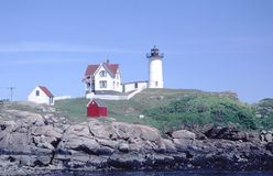 Nubble Light at Cape Neddick. Lighthouse located at near the entrance to York River in Maine. White tower with black lantern and outbuildings including red Stock Image