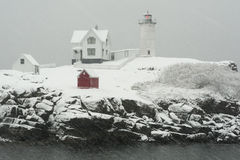Nubble Lighthouse in Winter Snowstorm. Maine's Nubble Lighthouse shines brightly during snowstorm Royalty Free Stock Photos