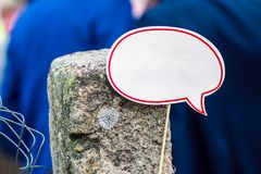 Nube blanca del discurso con el espacio de la copia en un palillo atado a una columna concreta vieja en el fondo de la gente en r fotografía de archivo