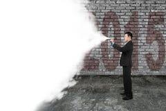 Nube blanca del espray del hombre de negocios que cubre la pared de ladrillo vieja de la oscuridad 2015 Imagenes de archivo