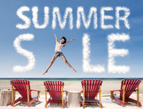 Nube de la venta del verano con la muchacha que salta sobre sillas de playa Foto de archivo libre de regalías