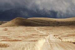 Nube de tormenta que pasa a través de una pista estéril de la montaña Imagen de archivo