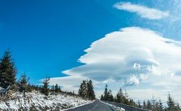 Nube lenticular cerca de la montaña Nube de los lenticularis del Altocumulus en el cielo azul Bosque y camino en primero plano imagen de archivo libre de regalías