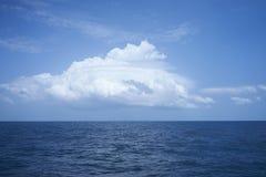 Nube sobre el océano ondulado en día soleado fotografía de archivo
