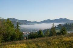 Nube sobre el pueblo en las montañas Imagenes de archivo