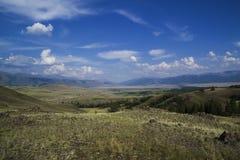 Nube sobre el rango de montaña Cielo azul e hierba verde en un valle Imagen de archivo libre de regalías