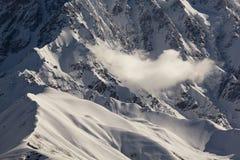 Nube sobre picos de montaña de la nieve Imágenes de archivo libres de regalías