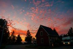 Nubes anaranjadas en la puesta del sol sobre la tierra que acampa Fotografía de archivo libre de regalías
