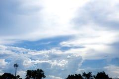 Nubes azules con el árbol en el primero plano Imagen de archivo libre de regalías
