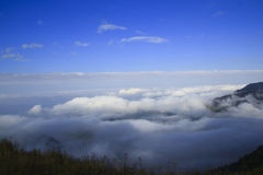 Nubes bajas, montañas y cielo azul Foto de archivo