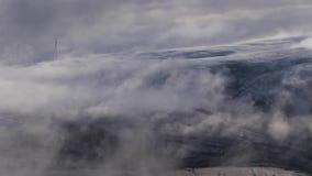 Nubes bajas que derivan además de las montañas durante la salida del sol, mostrando los molinoes de viento en la Escocia metrajes