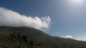 Nubes blancas, gruesas que se mueven rápidamente en pico de montaña en día claro almacen de video