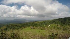 Nubes blancas, gruesas que se mueven rápidamente en pico de montaña en día claro metrajes