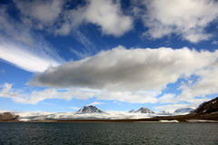 Nubes blancas hinchadas, cielo azul, picos de montaña y glaciares en el Svalbard ártico Foto de archivo
