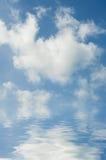 Nubes blancas mullidas en el cielo azul reflejado en ondulaciones del agua Fotos de archivo libres de regalías
