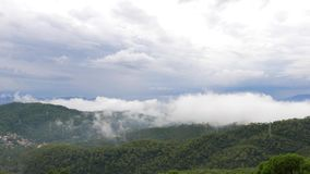 Nubes blancas que se encrespan del vuelo bajo de Timelapse sobre las montañas, Barcelona metrajes