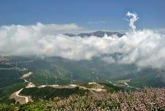 Nubes blancas sobre las colinas verdes y los molinos de viento Fotografía de archivo