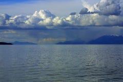 Nubes, cielo, agua, y montañas Imagenes de archivo
