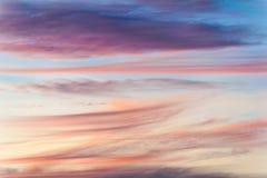 Nubes coloridas con diversas formas en el cielo con rosas, rojos y púrpuras como los movimientos del cepillo de una pintura fotografía de archivo